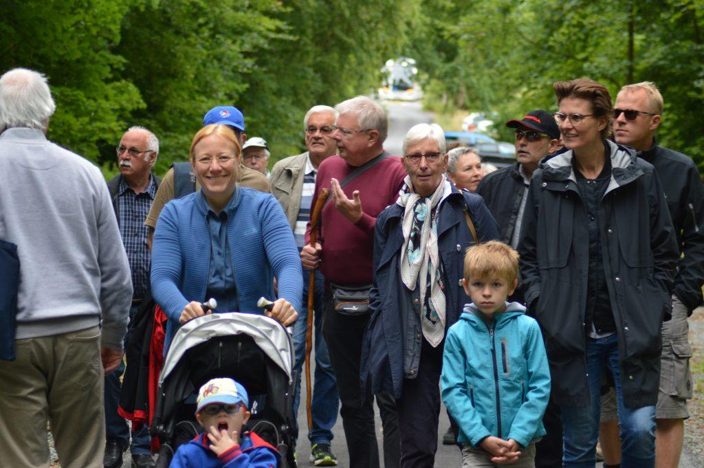 Ausflugsteilnehmenden gehen in Gruppe auf Waldweg auf Fotografin zu. In der Mitte Dagmar Schmidt mit Kinderwagen.